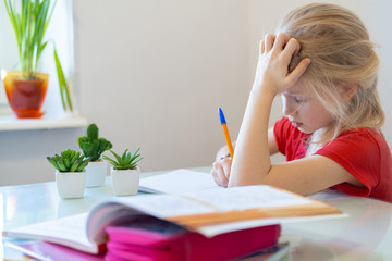 Serios blonde schoolgirl sitting at home and doing school homework, writing in notebook. Training...