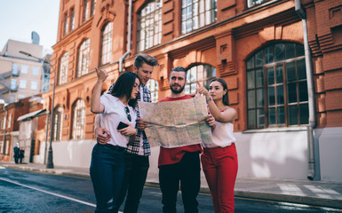 Calm adult lost travelers with paper map asking for advice locals on street in city