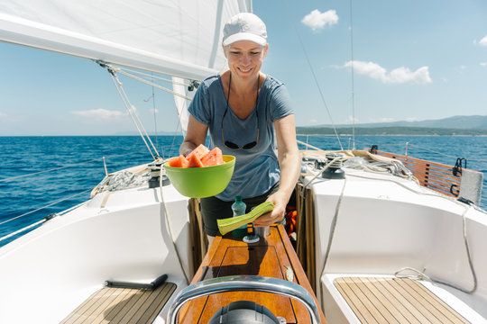 Woman on the deck of a sailboat serving fresh watermelons. Sailing and yachting concept.
