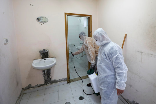 Members of a medical team spray disinfectants to sanitize a bathroom in a Red Crescent-run hospital which will be used for coronavirus quarantine, near Hebron in the Israeli-occupied West Bank