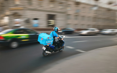 Minsk, Belarus. Jun 2019. Domino's delivery bike on the road. Delivery man riding moto bike, with motion blur effect. Food supplier driving fast on motorcycle to bring food to customer quickly