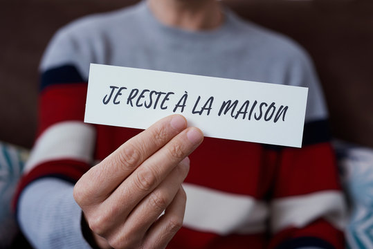 man showing the message I stay at home in french