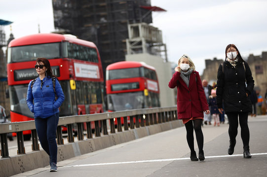 Women wearing protective face masks on Westminster bridge in Westminster as the number of coronavirus cases grow around the world.