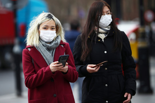 Women wearing protective face masks in Westminster as the number of coronavirus cases grow around the world.