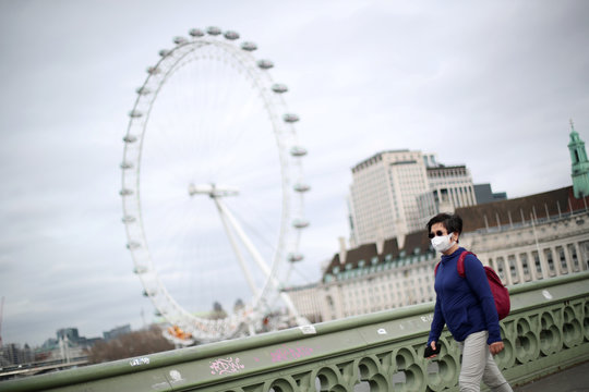 A woman walks on Westminster bridge in Westminster as she wears a protective face mask while the number of coronavirus cases grow around the world.