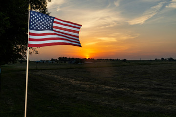 An amarican flag on the fence of a farm near the city of Commerce in the State of Oklahoma, at sunset, USA.