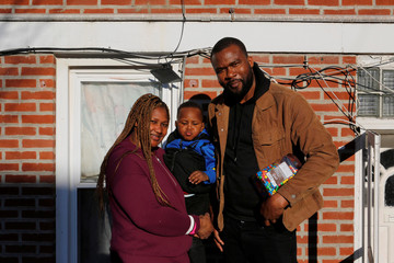 Uber and Lyft driver Adama Fofana poses for a picture with his wife and son in New York City