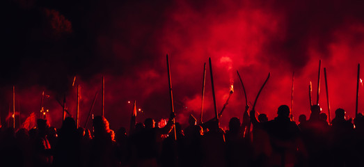 A medieval troop on the battlefield at night. Silhouettes of the fighting medieval soldiers on the red foggy background. Rebels during a riot with torches at night. Fototapete