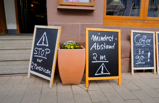 """Signs in front of a cafe and pastry shop indicate """"stop - just two persons at once"""" and """"keep at least two metres of distance"""" during the spread of the coronavirus disease (COVID-19) in Koenigsfeld"""