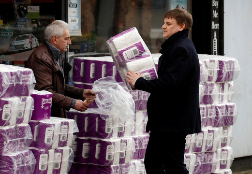 People buy toilet rolls on sale outside a car parts shop in Manchester, as the number of coronavirus cases grow around the world