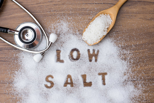 """White granulated natural sea salt in wooden scoop and words"""" Low salt """" letters written in salt grains and medical stethoscope on wood table background. Unhealthy food concept. Top view. Flat lay."""