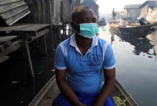 A man wearing a face mask sits in a traditional canoe at the Makoko community in Lagos