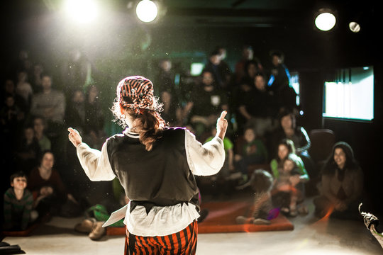 A performing arts entertainer is seen from the back in selective focus, dressed as a pirate on stage during a comedy act with blurry audience at back.