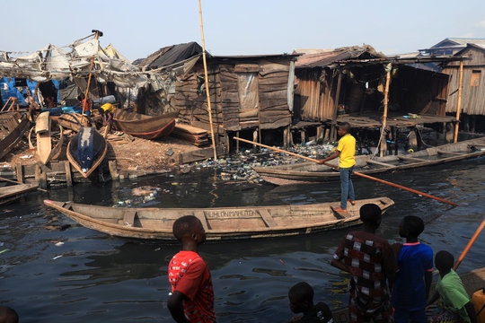 A boy paddles a traditional canoe at the Makoko community in Lagos