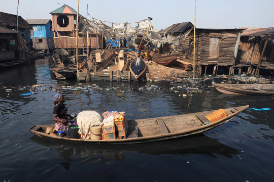 A woman hawks food items inside a traditional canoe at the Makoko community in Lagos