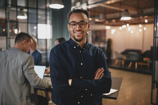 Smiling young businessman standing in a modern office