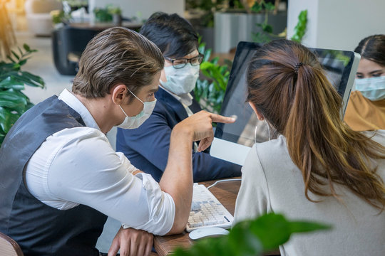 Business owner is handsome, wearing a surgical mask, thinking of planning and solving business problems with the team at co working space modern office .Health and teamwork concept