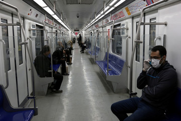 People wear protective face masks, following the outbreak of coronavirus, as they sit in a metro in Tehran