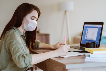 woman study at home with medical mask on face. coronavirus quarantine remote student home education concept.