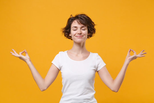 Smiling young brunette woman in white t-shirt isolated on yellow orange background. People lifestyle concept. Mock up copy space. Hold hands in yoga gesture, relaxing meditating, keeping eyes closed.