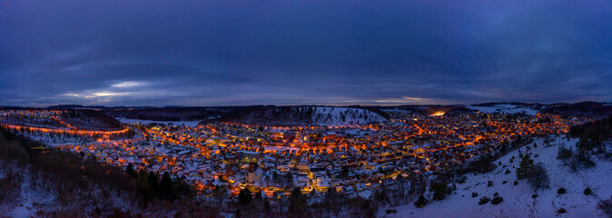Snowy cityscape of the town Albstadt in Baden Wuerttemberg, germany at the late evening hour with glowing lights.