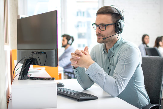 Customer service support operator man with headphones and microphone listening to his client in call center