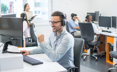 Fototapeta Male technical support operator with headset working in call center obraz