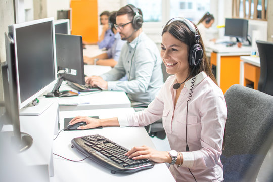 Young female technical support with hands-free device at call center