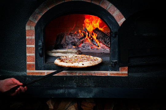 Cook makes pizza in the oven.