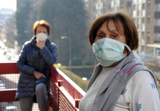 Europe, Italy, Milan - Pandemic emergency n-cov19 Coronavirus - Domestic life in quarantine of 70 year old lady who carries out various activities at home with the mask speaking 1 meter distance