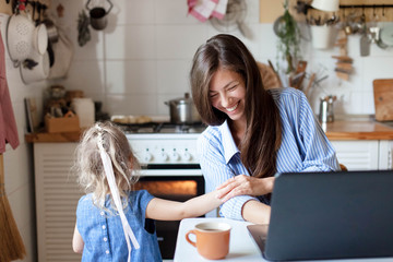 Working mom works from home with kid. Happy mother and daughter have fun. Successful woman and cute...