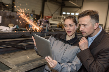 Female worker explains idea to her boss using a tablet