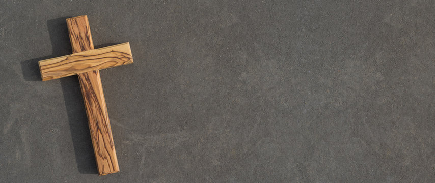 Holzkreuz liegt auf dunkler Steinplatte