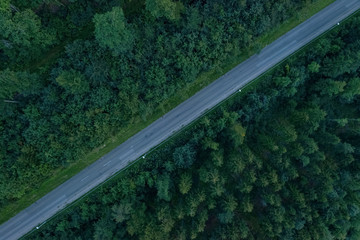 A street through a forest from top view, filmed by a drone, diagonal line, dividing the photo into two equal parts.
