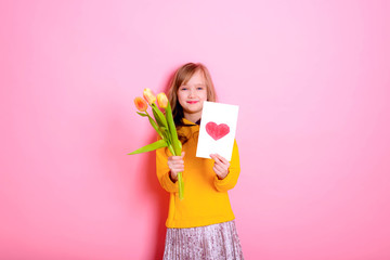 Happy Easter! Girl kid blonde in rabbit ears holding a card red heart, yellow tulips. Happy Mother's Day! International Women Day. Daughter's day.