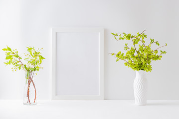 Mockup with a white frame, spring flowers in a vase and branches with green leaves on a light background