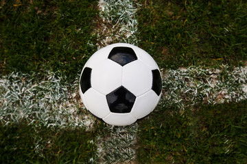 Classic soccer ball, typical black and white pattern, placed on the white marking line of the stadium turf. Traditional football ball on the green grass lawn with copy space.