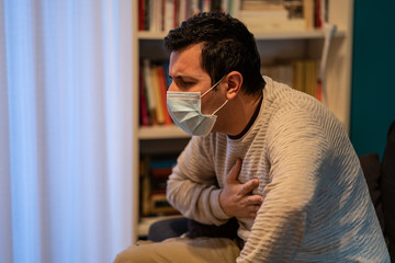 Man in a medical mask coughs and feels sick handning on chest, experiencing pain. Concept of the spread of the pandemic covid 19 corona virus.