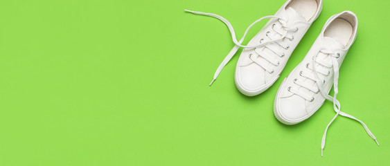 White female fashion sneakers on green background. Flat lay top view copy space. Women's shoes. Stylish white sneakers. Fashion blog or magazine concept. Minimalistic shoe background, sport shoes Wall mural