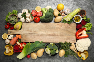 Fresh products and wooden board with space for text on grey table, flat lay. Healthy cooking Fotobehang