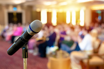 Close up of Microphone on stage, abstract blurred of speech in seminar room or speaking conference hall light, Event Background ,Shallow depth of field