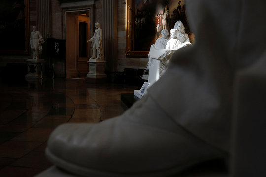 Statues are illuminated by sunlight inside of an empty U.S. Capitol Rotunda, following the government's notice to halt all public building tours due to COVID-19 on Capitol Hill in Washington
