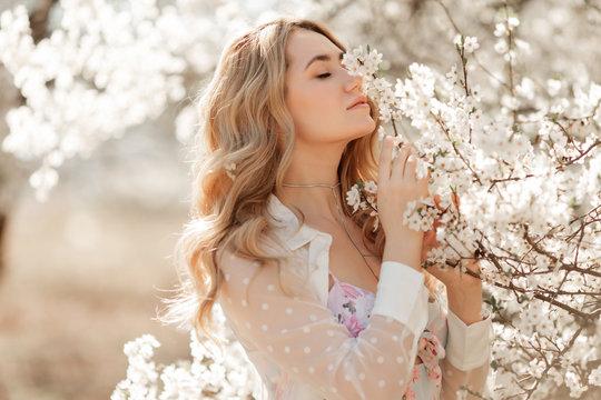 Pretty woman in blossom spring garden