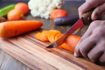 Closeup image of a man cutting and chopping carrot by knife on wooden board