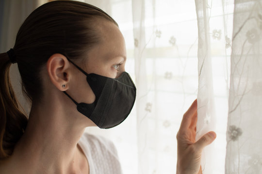Woman at home in self isolation quarantine, staying at home looking out window with face mask on. Coronavirus 2019-ncov.