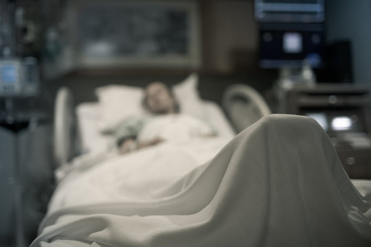 Sick woman in hospital bed unrecognizable.