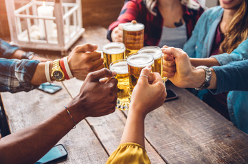 Group of people enjoying and toasting a beer in brewery pub - Friendship concept with young people having fun together