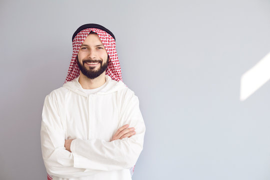Attractive smiling arab man crossed his arms on a gray background