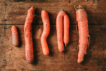 Ugly misshapen carrots on wooden background. Concept of zero waste production. Top view. Copy space. Non gmo vegetables