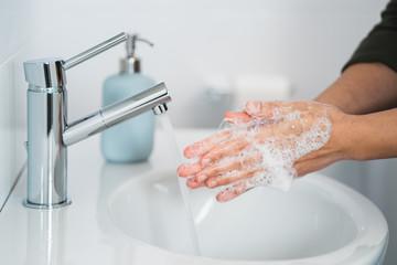 Obraz Hygiene. Cleaning Hands. Washing hands with soap. Young woman washing hands with soap over sink in bathroom, closeup. Covid 19. Coronavirus. - fototapety do salonu